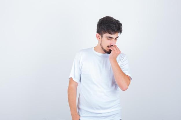 Giovane in maglietta che si mangia le unghie e sembra preoccupato