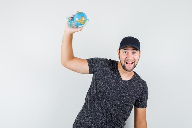 Giovane in maglietta e berretto che tiene il globo del mondo e che sembra allegro
