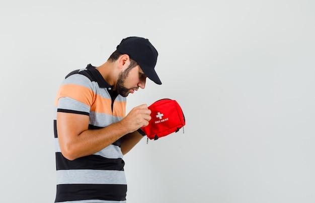 Giovane uomo in t-shirt, cappuccio che esamina il kit di pronto soccorso e che sembra curioso.