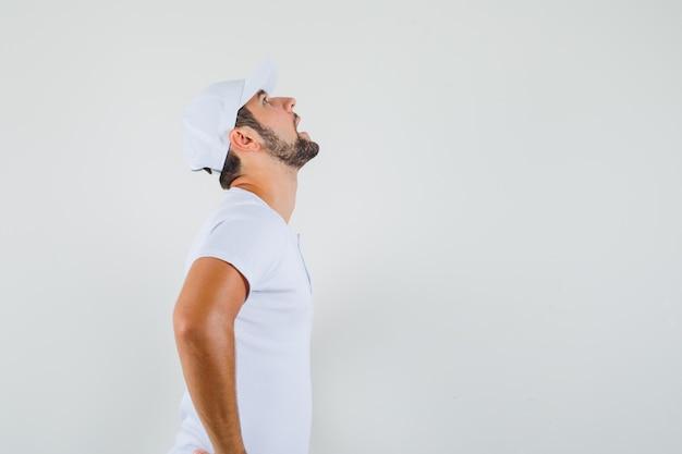Giovane uomo in t-shirt, cappello alzando lo sguardo e guardando turbato, vista frontale. spazio libero per il testo