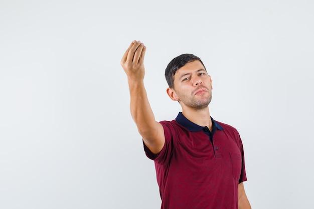 Giovane in maglietta che fa gesto italiano, vista frontale.