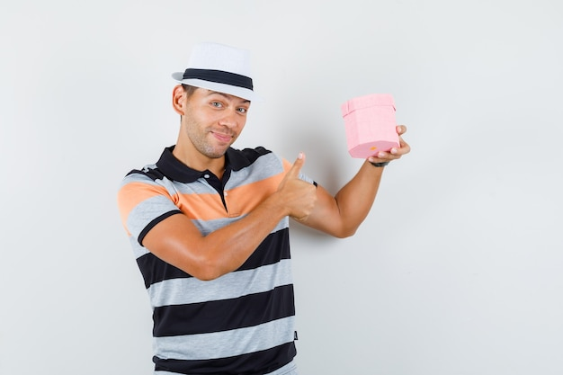 Young man in t-shirt and hat holding present box with thumb up and looking cheerful