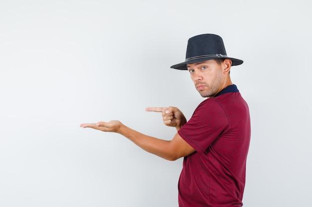 Giovane in t-shirt, cappello che punta via con il palmo aperto e sembra sicuro.