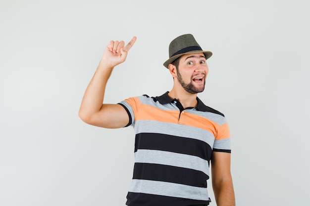 Young man in t-shirt, hat pointing to the side with finger up and looking curious , front view.