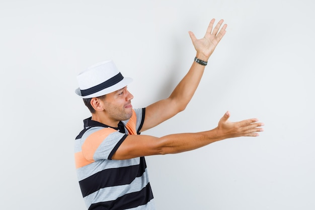 Young man in t-shirt and hat raising hands and looking sorrowful .