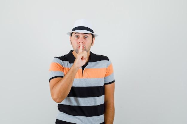Giovane uomo in t-shirt, cappello che mostra gesto silenzioso e guardando attento