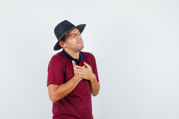 Giovane uomo in t-shirt, cappello che soffre di dolore al petto e sembra malato, vista frontale.