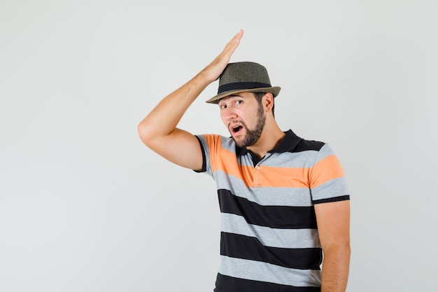 Giovane uomo in t-shirt, cappello che tocca la fronte con il palmo e guardando dispiaciuto, vista frontale.