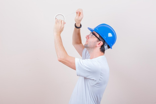 Young man in t-shirt, helmet opening roll of duct tape and looking careful