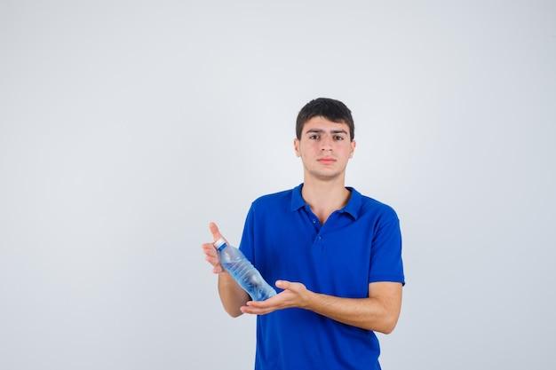 Giovane uomo in t-shirt tenendo la bottiglia di plastica nelle mani e guardando fiducioso, vista frontale.