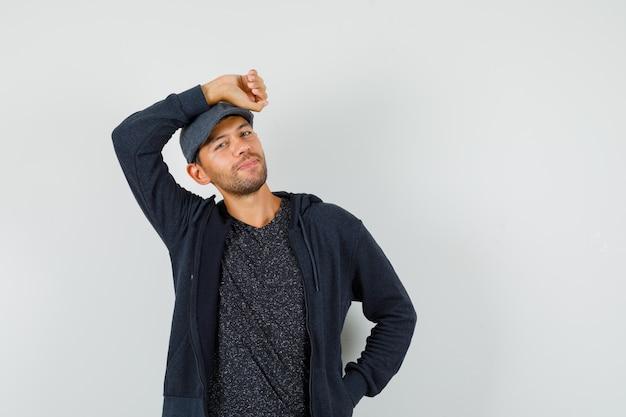 Giovane uomo in t-shirt, giacca, berretto tenendo il braccio alzato sopra la testa e guardando bello, vista frontale.