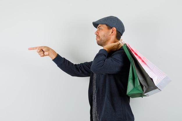 Giovane uomo in t-shirt, giacca, berretto che tiene le borse della spesa, indicando la parte anteriore di lui.