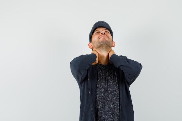 Giovane uomo in t-shirt, giacca, berretto alzando lo sguardo, tenendo le mani sul collo e guardando tranquillo, vista frontale