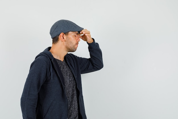 Young man in t-shirt, jacket, cap rubbing eyes and nose and looking fatigued , front view.