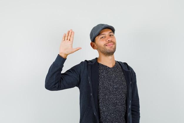 Giovane uomo in t-shirt, giacca, berretto agitando la mano per salutare e sorridere, vista frontale.