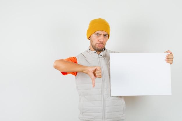 Giovane uomo in t-shirt, giacca, cappello che tiene tela bianca, mostrando il pollice verso il basso e guardando deluso, vista frontale.