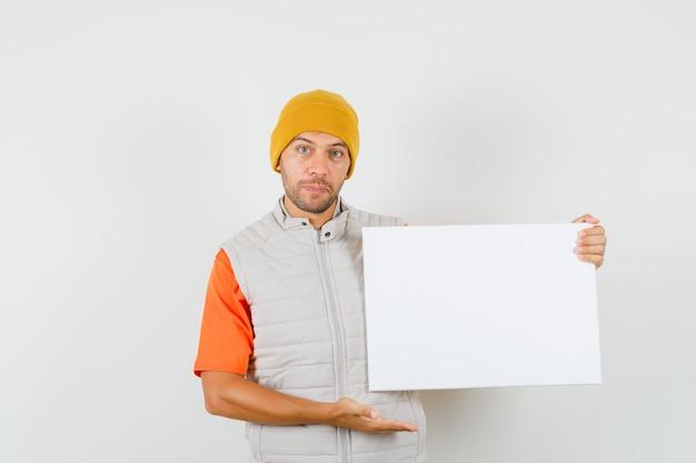 Giovane uomo in t-shirt, giacca, cappello che mostra tela bianca e sembra positivo