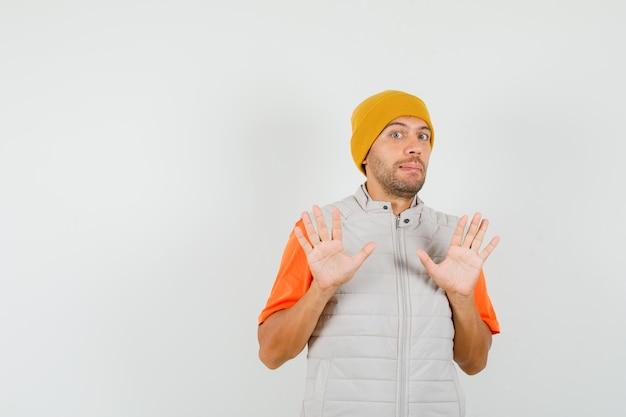 Giovane uomo in t-shirt, giacca, cappello che non mostra alcun gesto e sembra spaventato, vista frontale.