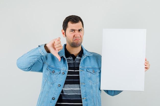 Giovane uomo in t-shirt, giacca in possesso di tela bianca, mostrando il pollice verso il basso e guardando insoddisfatto