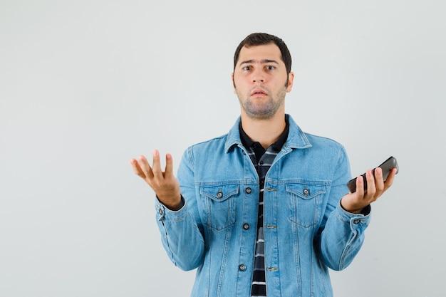 Giovane uomo in t-shirt, giacca in possesso di calcolatrice e guardando confuso