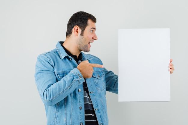 Giovane uomo in t-shirt, giacca che punta alla tela bianca e sembra allegro