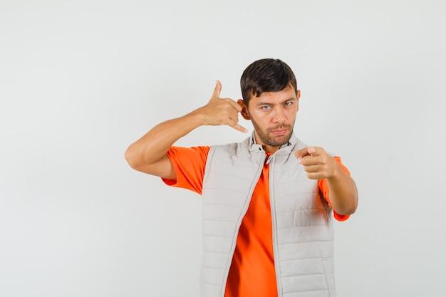 Giovane uomo in t-shirt, giacca che mostra il gesto del telefono mentre punta verso di te, vista frontale.