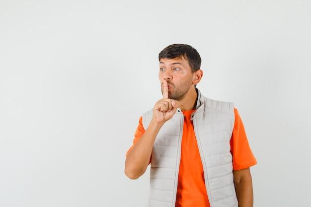 Giovane uomo in t-shirt, giacca che mostra il gesto di silenzio e guardando attento, vista frontale.