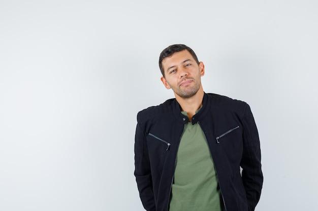 Giovane uomo in t-shirt, giacca in piedi con le mani in tasca e dall'aspetto elegante, vista frontale.