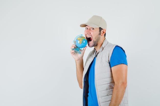 Giovane uomo in t-shirt, giacca cercando di mordere il globo della scuola e guardando divertente, vista frontale.