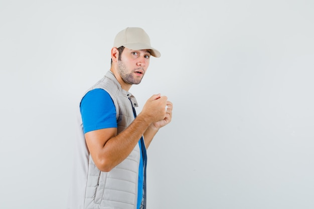 Giovane uomo in t-shirt, giacca che cerca di indossare una mascherina medica e sembra ragionevole.