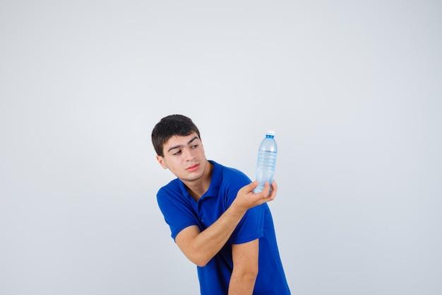 Giovane uomo in t-shirt tenendo la bottiglia di plastica in mano e guardando fiducioso, vista frontale.