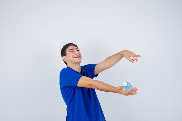 Giovane uomo in maglietta tenendo in mano la bottiglia di plastica, indicando il lato destro e guardando felice, vista frontale.