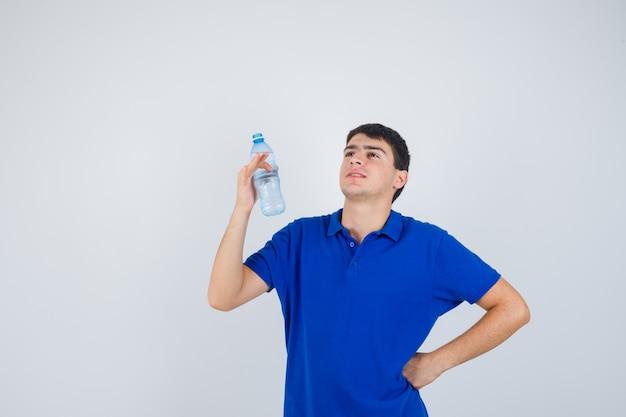 Giovane uomo in t-shirt mantenendo la bottiglia di plastica, tenendo la mano sulla vita e guardando fiducioso, vista frontale.
