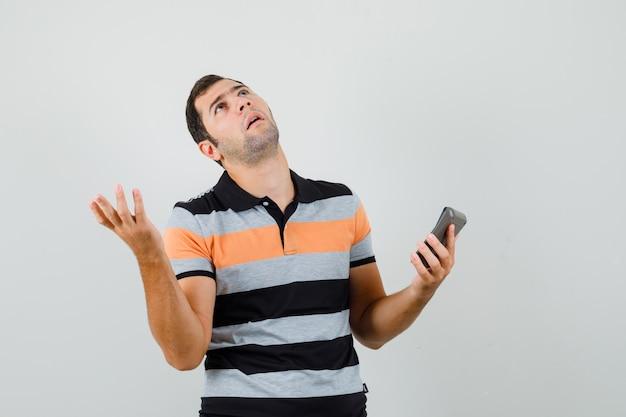 Giovane uomo in maglietta alzando lo sguardo dopo aver letto il messaggio e guardando turbato