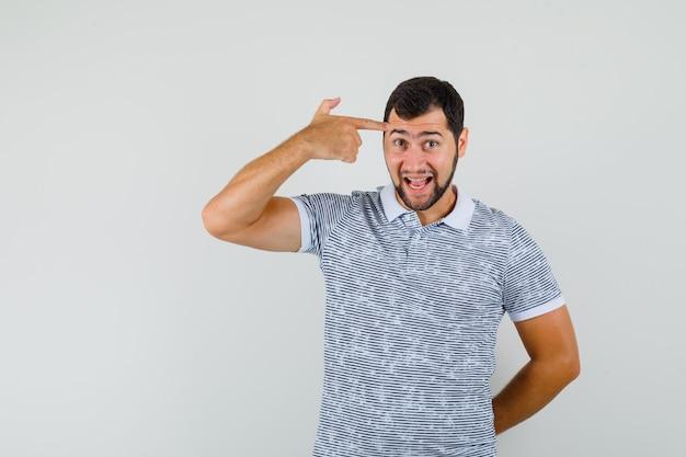 Giovane uomo in maglietta che fa gesto di suicidio e guardando divertito, vista frontale.