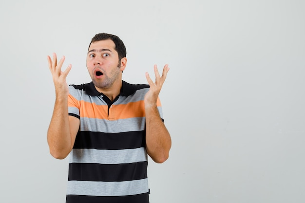 Giovane uomo in t-shirt che mostra gesto impotente e cerca spazio libero travagliato per il tuo testo