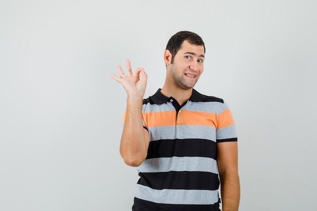 Giovane in maglietta che mostra gesto giusto e che sembra soddisfatto