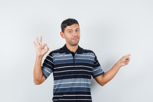 Giovane uomo in t-shirt che mostra segno ok mentre indica il lato e sembra allegro, vista frontale.