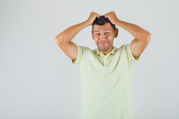 Young man in t-shirt tearing his hair and looking negative