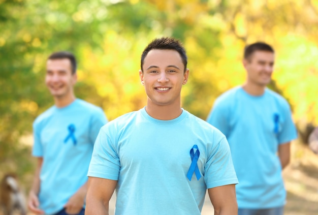 Young man in t-shirt with blue ribbon outdoors. prostate cancer awareness concept