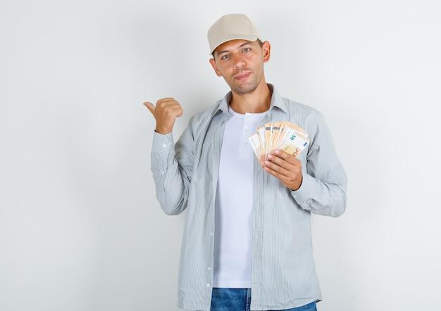 Giovane uomo in t-shirt con cappuccio, jeans che punta lontano con i soldi