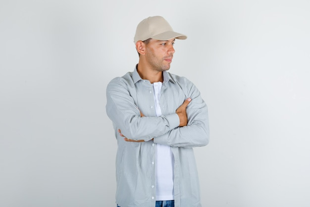 Young man in t-shirt with cap, jeans standing with crossed arms