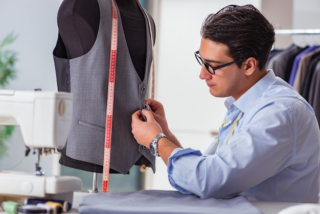 Young man tailor working on new clothing