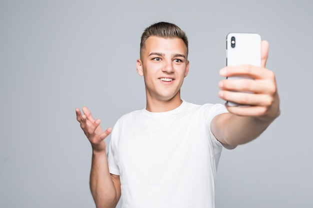Young man take selfie isolated on gray