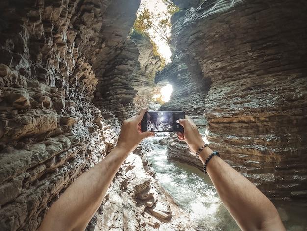 Молодой человек фотографирует со своего мобильного телефона в каньоне.