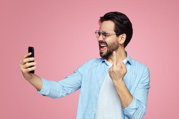 Молодой человек делает селфи и показывает средний палец в камеру над розовой стеной