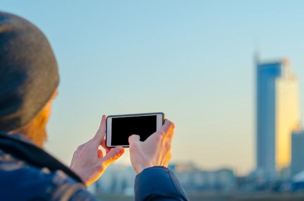 Молодой человек фотографирует город на смартфоне