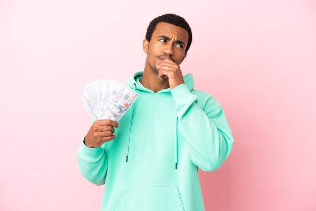 Молодой человек берет много денег на изолированном розовом фоне и смотрит вверх