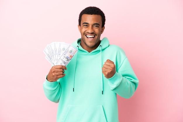 Молодой человек берет много денег на изолированном розовом фоне, празднует победу в позиции победителя Premium Фотографии