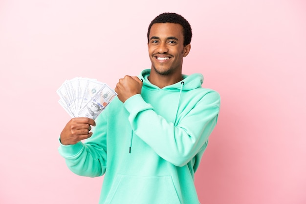 Молодой человек берет много денег на изолированном розовом фоне, празднует победу Premium Фотографии